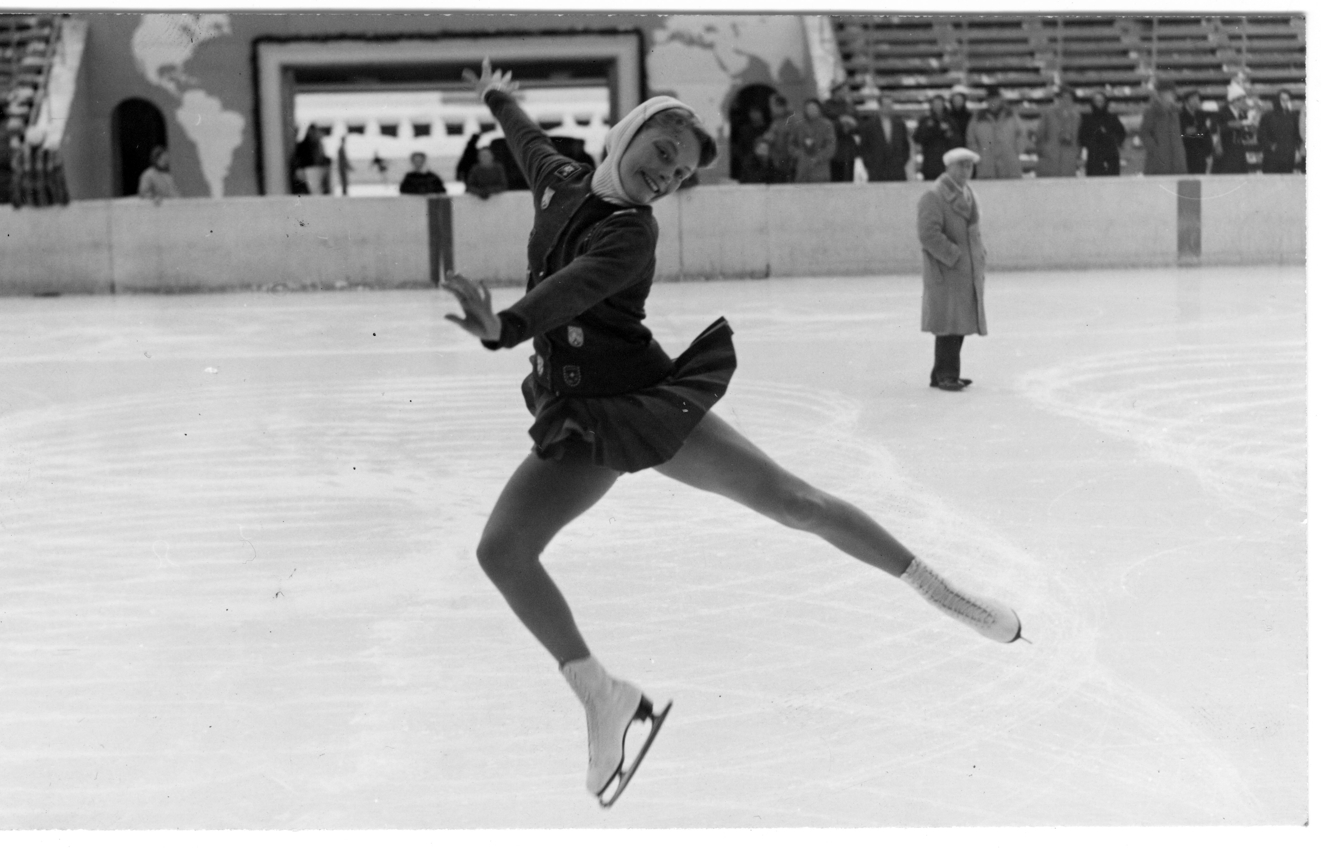 Carol Heiss performs a mid-air arabesque in a black and white photo in an indoor ice rink,