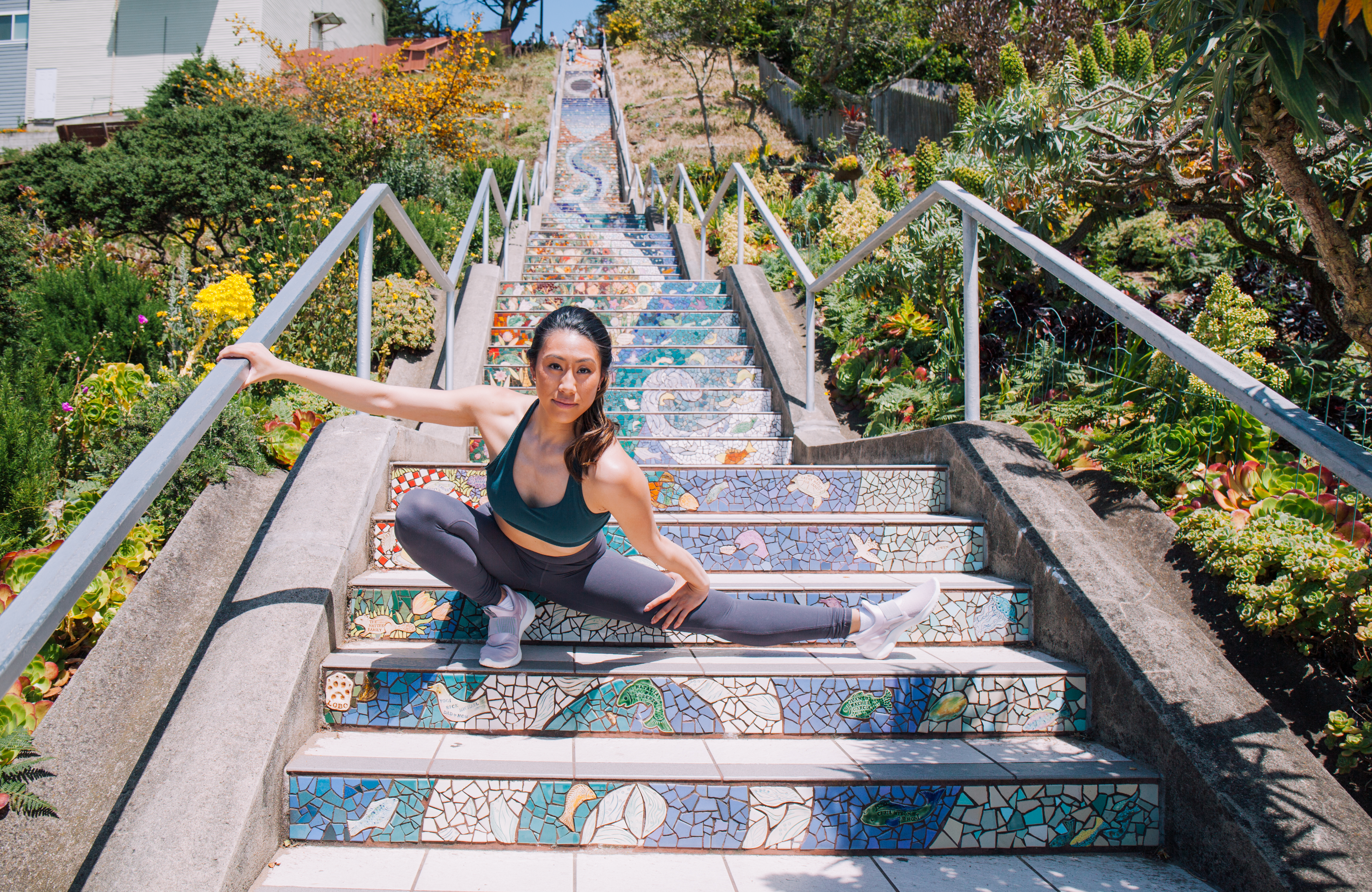 Michelle Hong demonstrates a side lunge on outdoor steps.