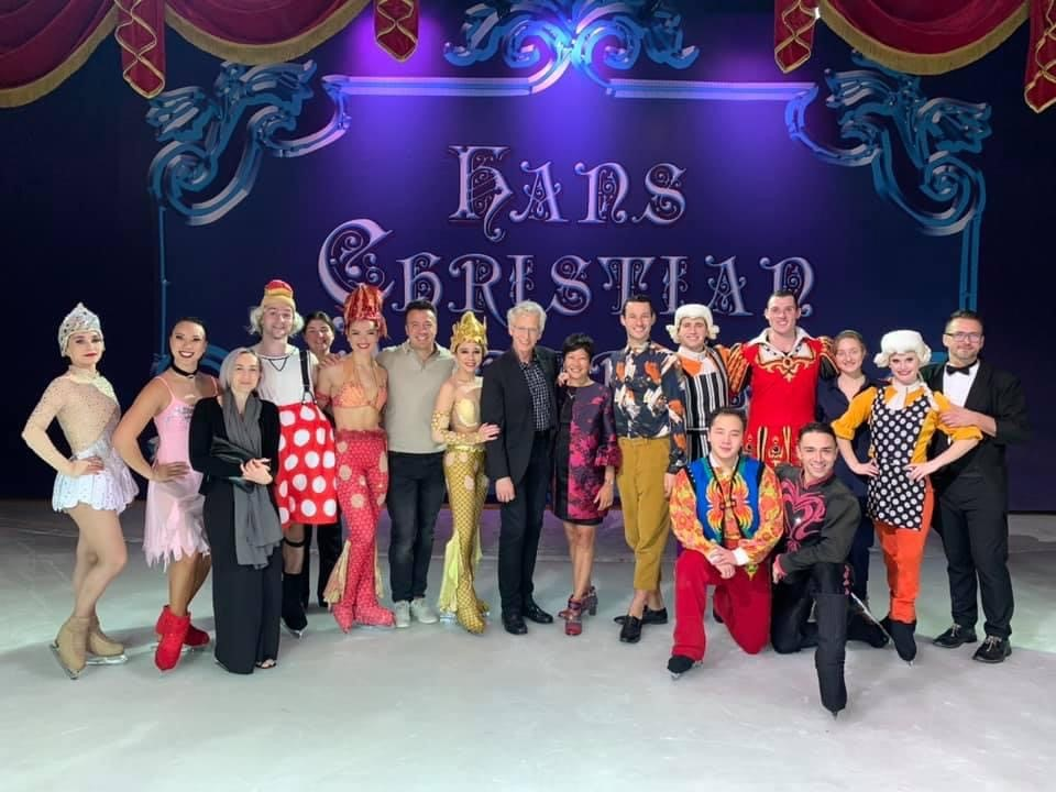 A cruise ship skating show group poses on the ice with Sarah Kawahara.