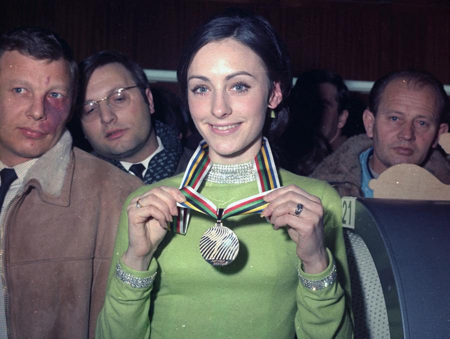 Peggy Fleming shows off her 1968 Olympic medal wearing her iconic green dress.