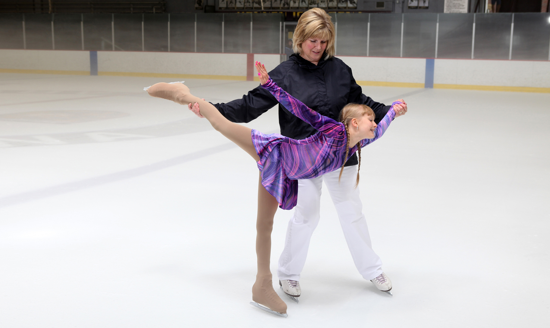 A coach helps a young skater.