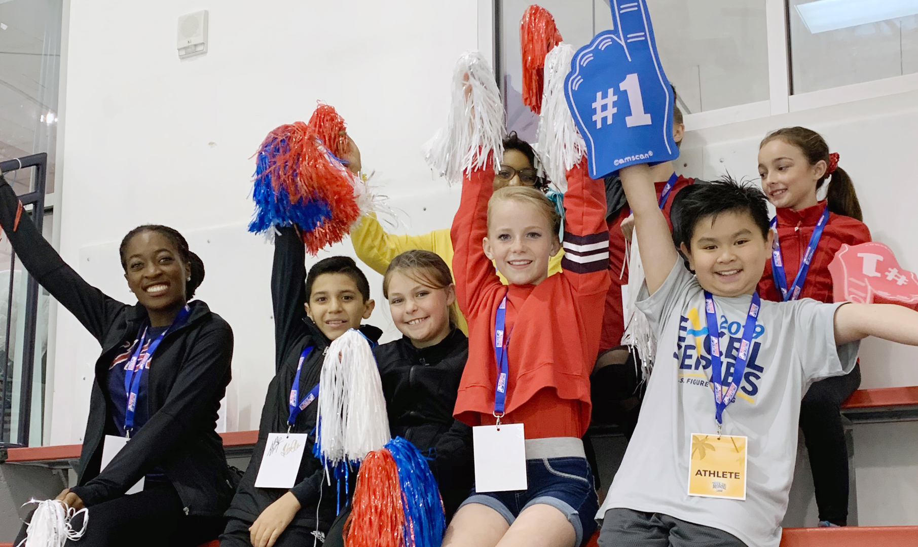 Athletes cheer on skaters at a competition.