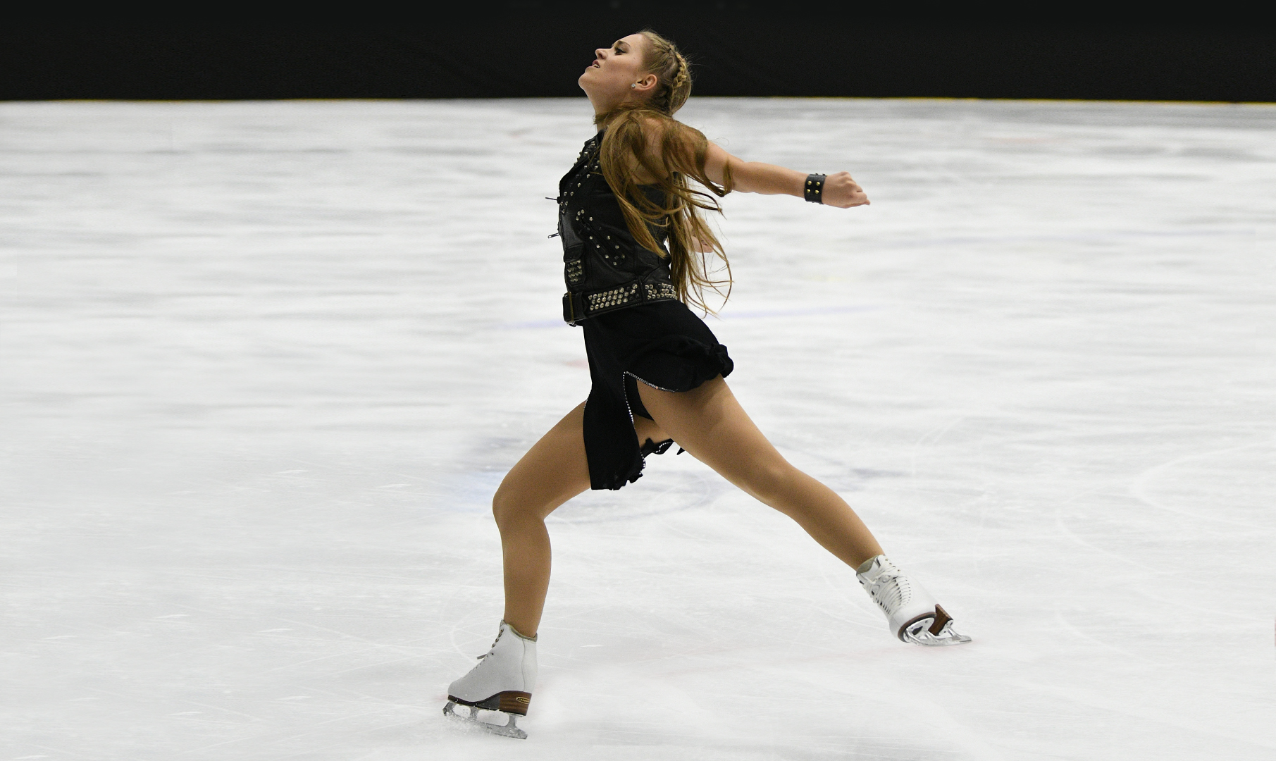Solo dance skater performs in front of a crowd.