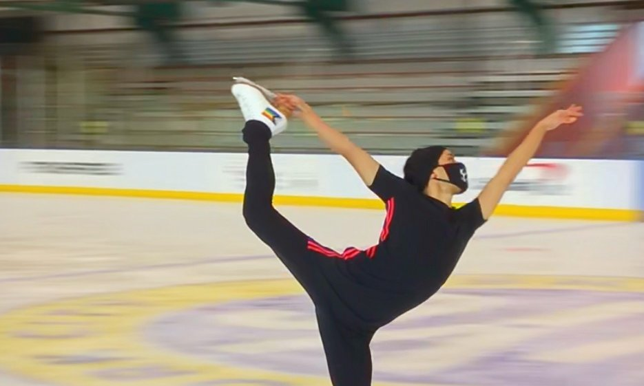 Eliot Halverson, dressed in all black, performs a catch-foot spiral on the ice.