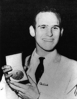 Dick Button shows his gold medal to the camera while smiling.
