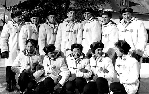 1956 U.S. Olympic Figure Skating Team, wearing white jackets, poses for the camera in an outdoor setting.