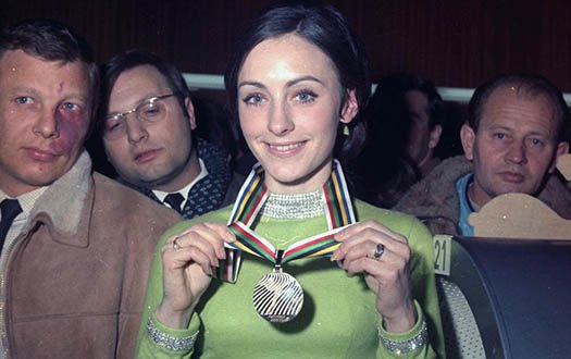 Peggy Fleming shows off her gold medal, surrounding by reporters, at the 1968 Olympic Games.