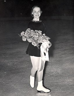 Carol Heiss poses with flowers while looking at the camera