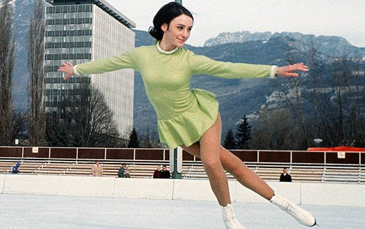 Peggy Fleming performs a crossover while wearing a green dress at the 1968 Olympic Games.