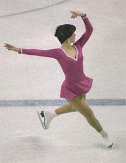 Dorothy Hammill, wearing a pink dress and white skates, performs a step sequence at the 1976 Olympic Winter Games.