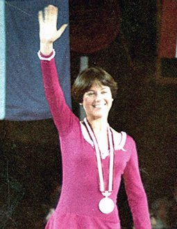 Dorothy Hammill waves to the crowd atop the podium at the 1976 Olympic Winter Games