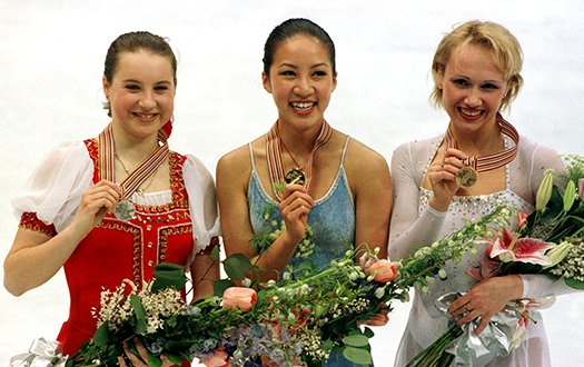 Michelle Kwan stands with silver medalist Irina Slutskaya (left) and bronze medalist Maria Butyrskaya (right) who are showing their medals to the camera while smiling.