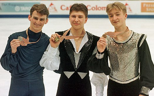 Tood Eldredge is joined by Alexei Yagudin (center) and Evgeni Plushenko (right), who are all showing their medals to the camera.