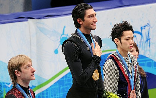 Evan Lysacek stands atop the podium with hand over his heart after winning the gold medal.