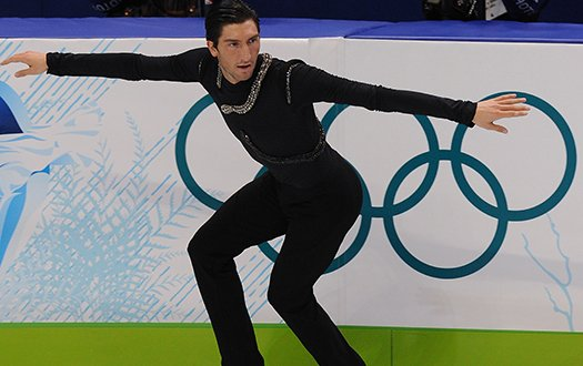 Evan Lysacek performs a backwards crossover in front of the Olympic rings.