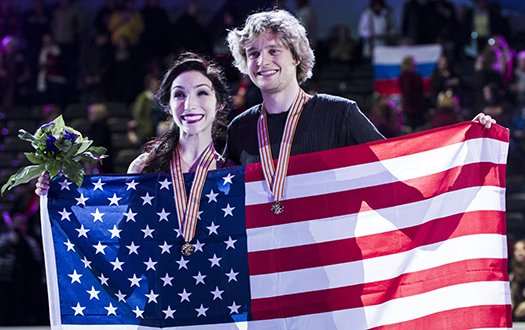 Meryl Davis and Charlie White pose with their medals and a flag at Worlds.