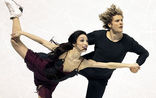 Meryl Davis skates with leg outstretched and Charlie White by her side at the 2013 World Championships.