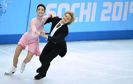 Meryl Davis, wearing pink, and Charlie White, wearing a suit, skate in front of the Sochi 2014 banner, while performing a step sequence.