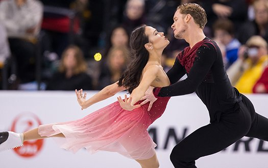 Madison Chock and Evan Bates stare into each other's eyes while performing a step sequence.