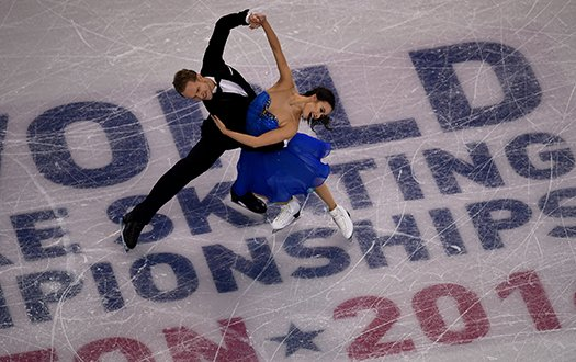 Madison Chock and Evan Bates perform a dance move over the in-ice event logo at the World Championships