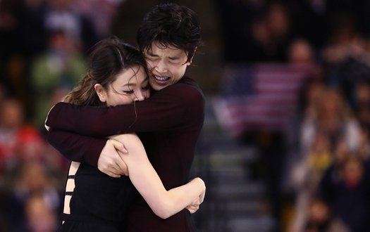 Maia and Alex Shibutani embrace on the ice after completing their program, as fans cheer in the background.