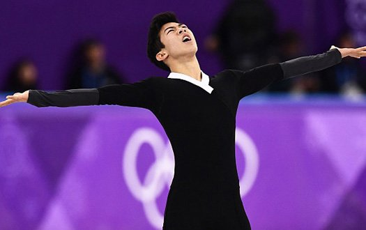 Nathan Chen looks to the sky with his arms outstretched as he completes his free skate.
