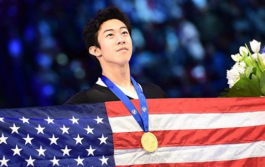 Nathan Chen looks towards the sky with a gold medal around his neck and an American flag in his hand.