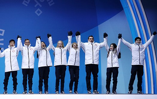 The Olympic Team event participants cheer while holding hands as they are awarded their medals.