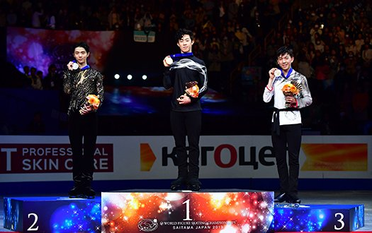 Nathan Chen stands atop the podium, with Yuzuru Hanyu to his right, and teammate Vincent Zhou to his left, hold his medal towards the camera.