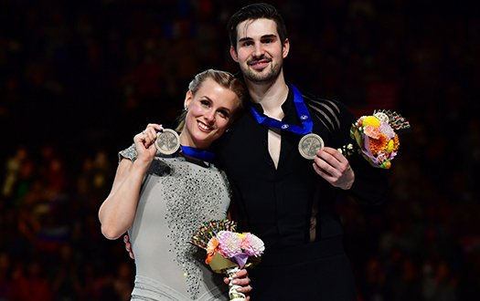 MAdison Hubbell and Zachary Donohue smile for the camera with medals in hand from the podium at the 2019 World Championships.