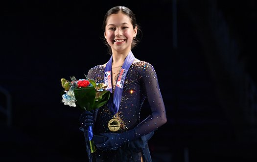 Alysa Liu with her medal atop the podium, smiles for the camera.