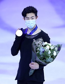 Nathan Chen poses with his gold medal and flowers while wearing a mask at the 2021 World Championships