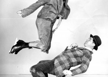 1930s show skaters Frick and Frack perform a jump and duck move together in a black and white staged photo.