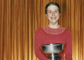 Patricia Shelley holds up a trophy on the podium post competition in 1972 wearing a faded red dress.