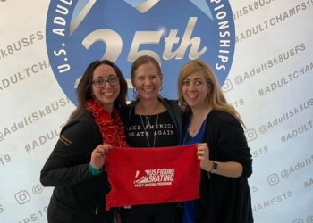 Past, present and future Adult Skating Committee chairs Aviva Cantor, Lori Fussell and Lexi Rohner at the 2019 U.S. Adult Championships holding up an adult skating towel.